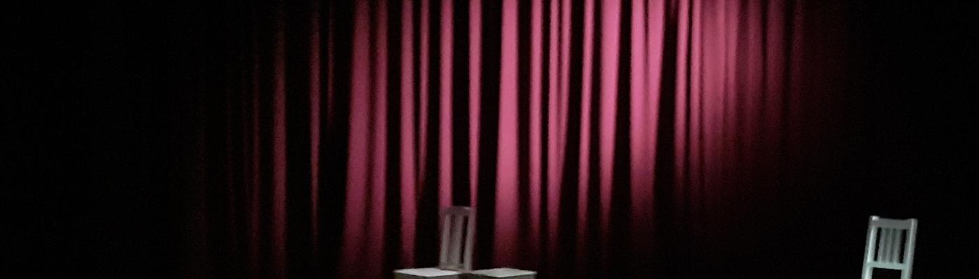 punainen esirippu ja kolme tuolia lavalla