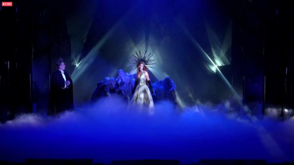 Usvan täyttämällä lavalla valojen keskellä kruunupäinen nainen, jota ympäröi kaapuihin puettu ihmisjoukko. Lavan sivulla frakkiin pukeutunut pystyhiuksinen ja silmälasipäinen mies